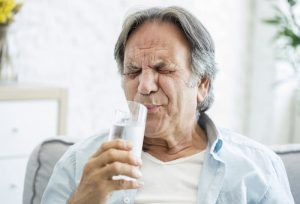 man in pain with tooth sensitivity to cold drink